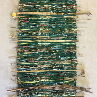Multi-fiber wall hanging in yellows, greens, and browns