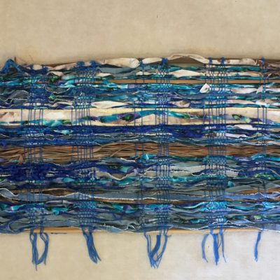 Multi-fiber wall hanging in blues, whites, and browns