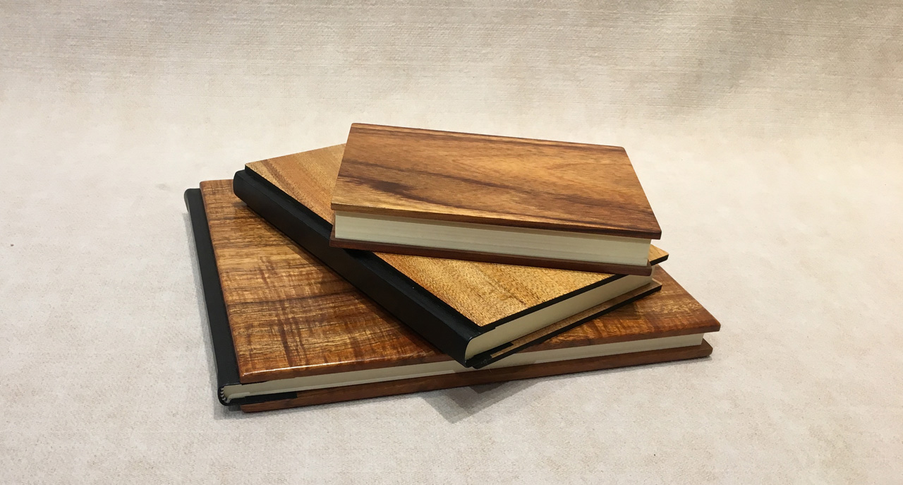 Stack of three koa journals