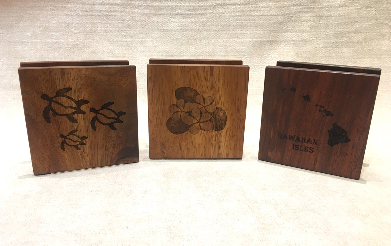 Three Koa Wood Napkin Holders with honu (turtles), plumeria, and Hawaiian Island designs
