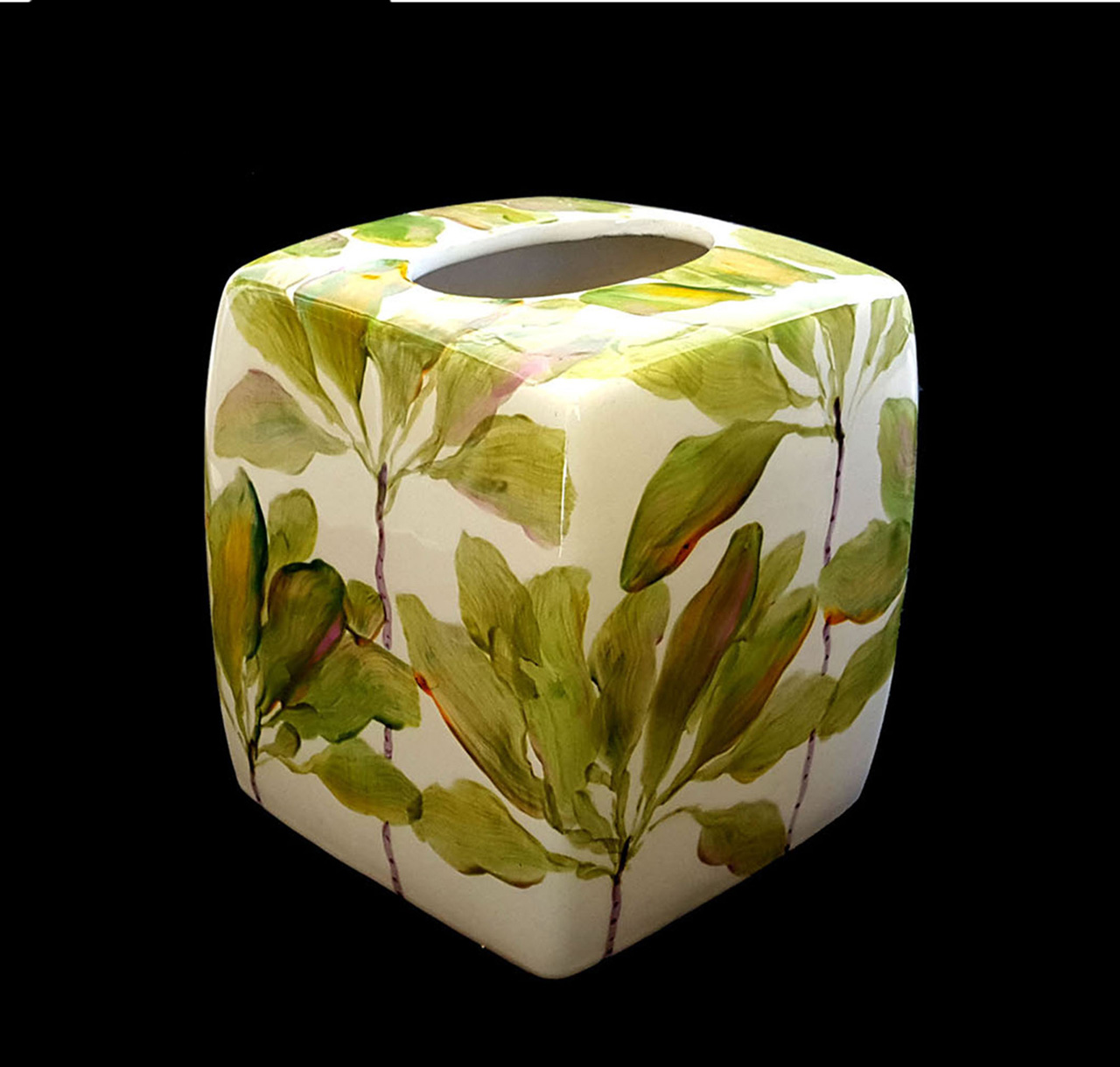 a ceramic tissue box holder with painted ti leaves