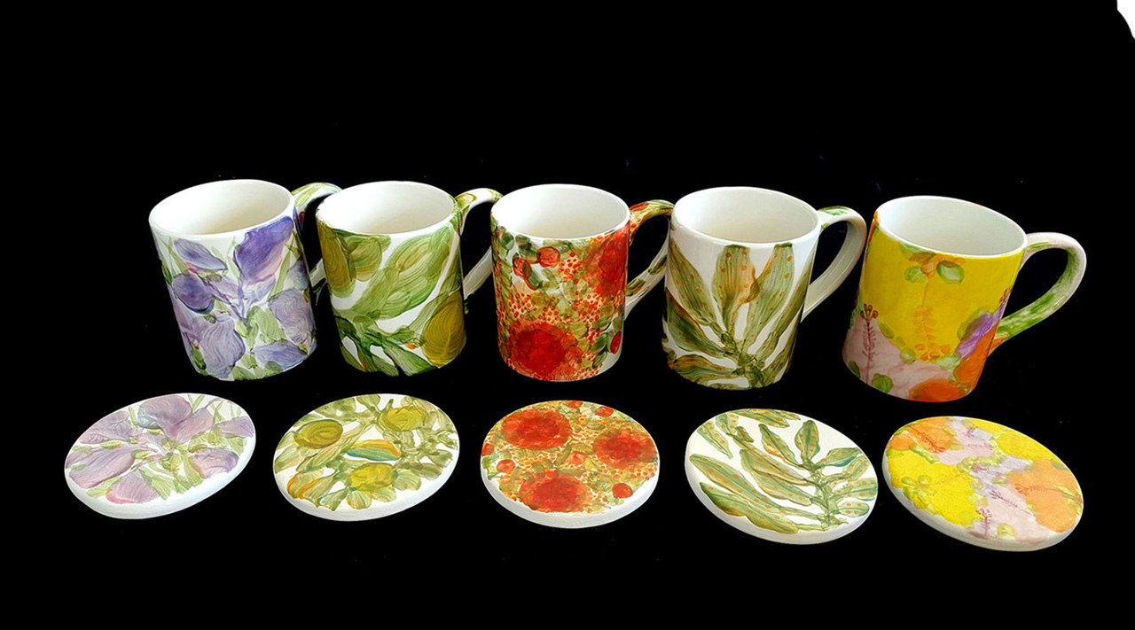 five hand painted mugs with their matching costers