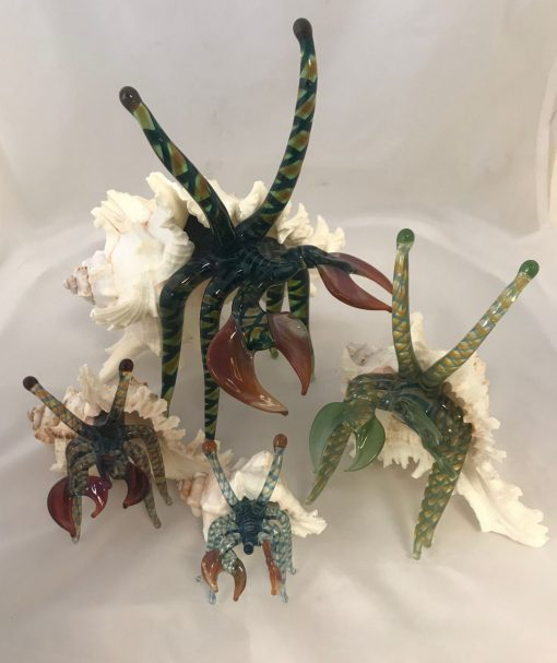 four glass hermit crab sculptures. assorted colors and four different sizes.