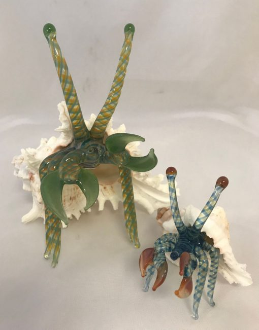 one large and one medium glass crab sculpture in their shells.