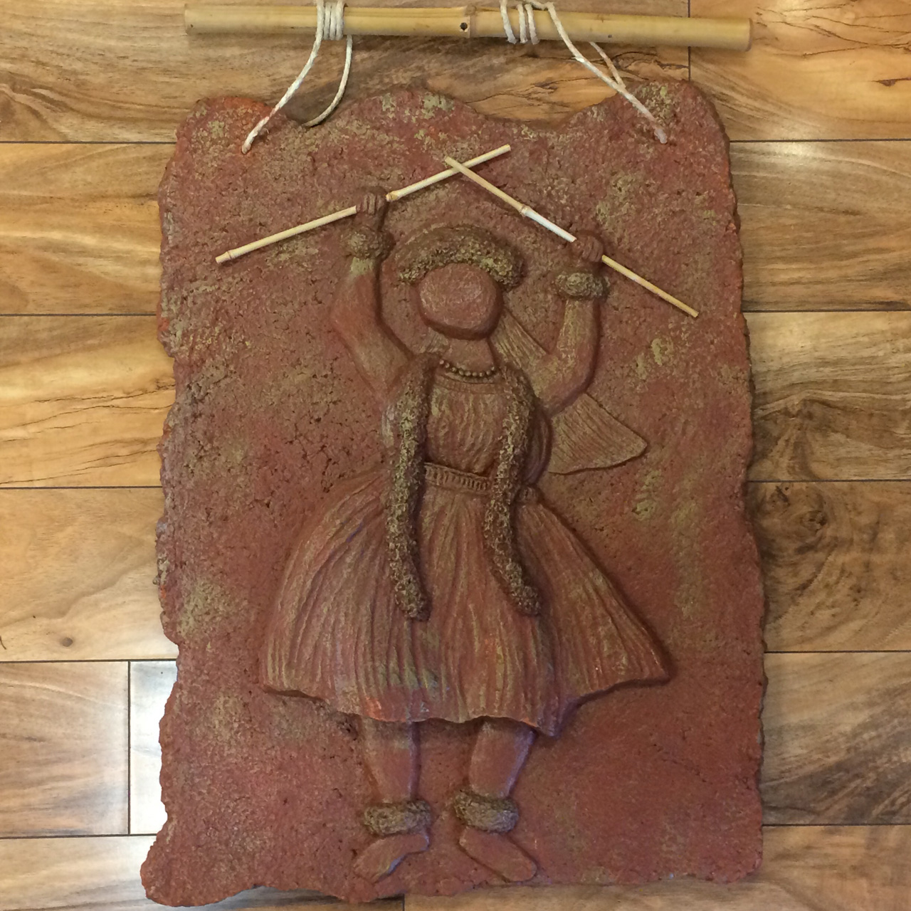 Hula Wahine by Kalei Engel depiciting a female hula dancer in Hawaiian red clay and paper medium and gold accents with natural bamboo hanger
