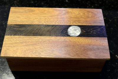 a rectangular box made of mostly light colored wood with a strip of dark wood going across the center with a coin in the middle