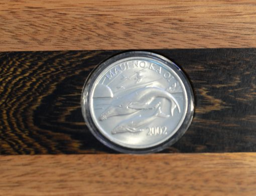 an up-close view of the coin that is in the secret box. Two whales