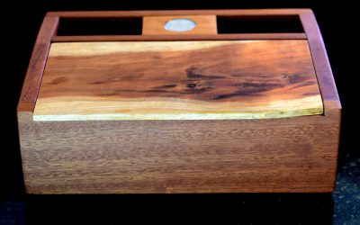 a rectangular box made of mahogany and koa with a coin towards the back hinge