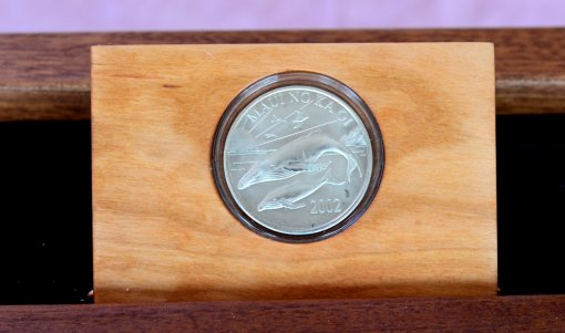 an up-close view of the coin in a dresser valet box. The coin is of two humpback whales