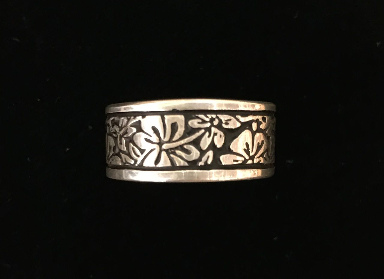 sterling silver band ring center hibiscus flowers around entire band. black in vacant spaces and bordered