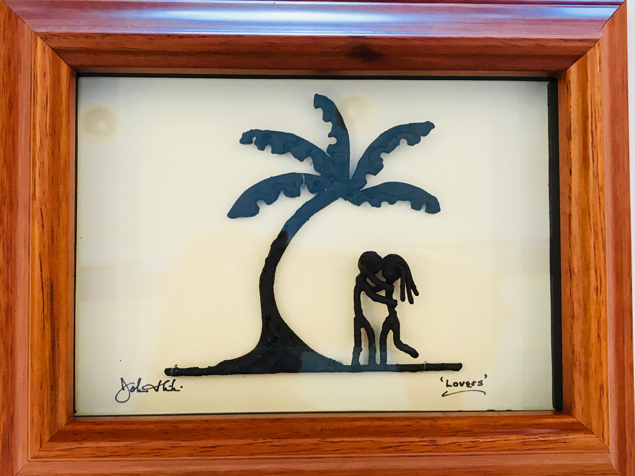 Framed metal sculpture of two people under a palm tree entitled Lovers by John Ilnicki