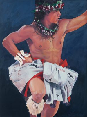 A male hula dancer in motion with one knee up and one hand towards the sky, wearing red and while hula attire