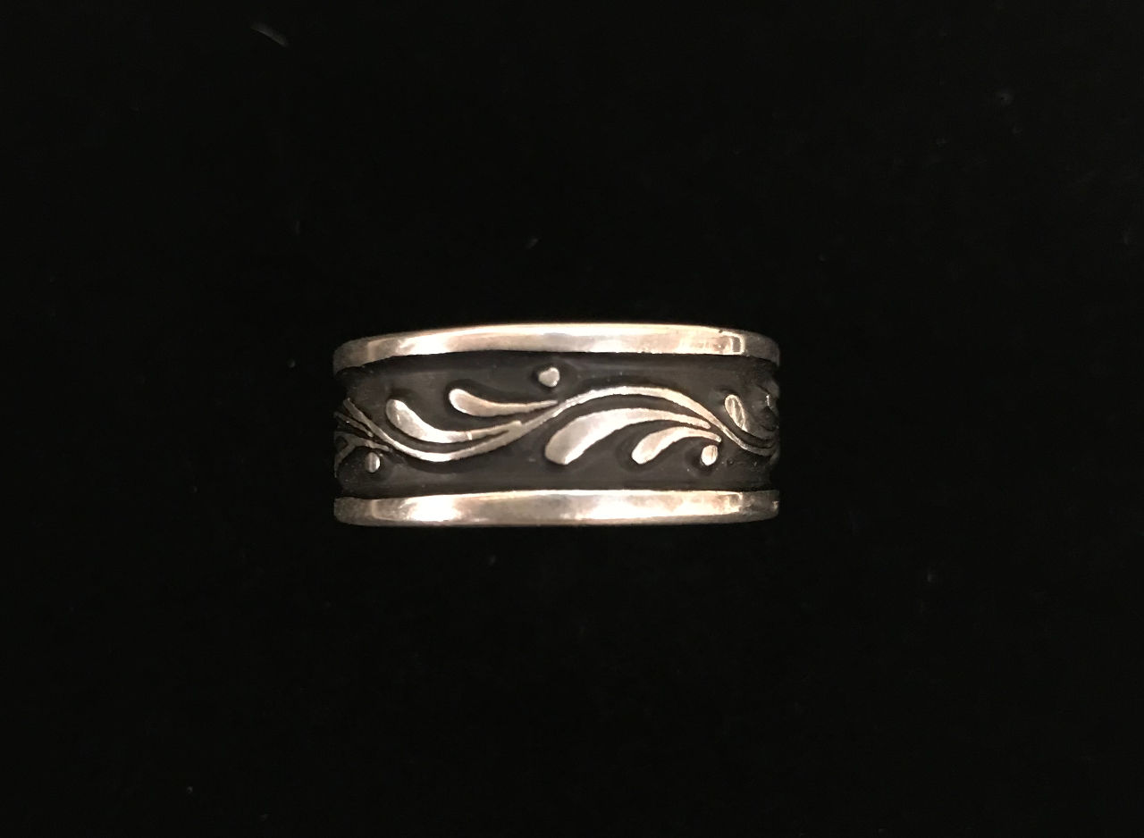 sterling silver symmetrical ring with dark center and silver flow lines and dots.