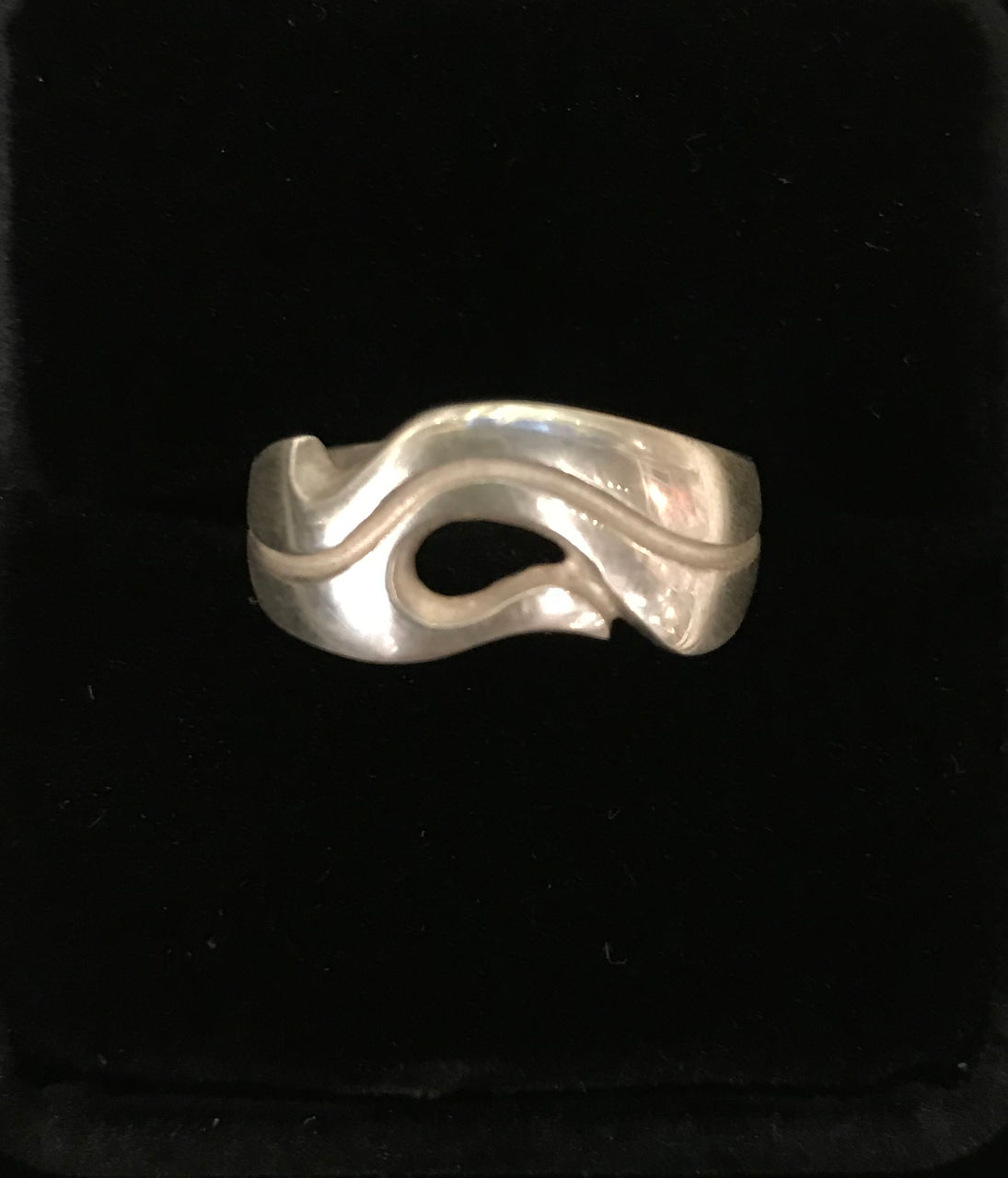 sterling silver ring flowing design with a single oval like opening and a line going around the entire ring