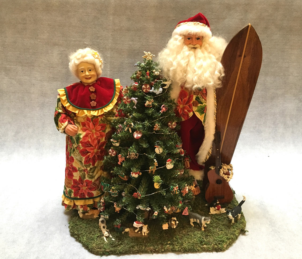 Mr. and Mrs. Santa Claus standing by Christmas tree