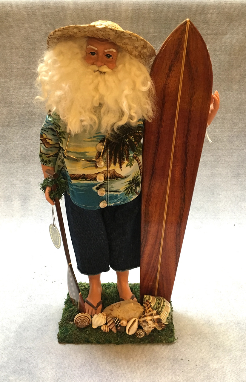 Santa in aloha shirt holding surfboard and paddle