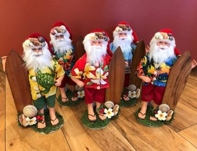 five Santa figures with a surf board, aloha shirt, slippers, and a chrismas hat.
