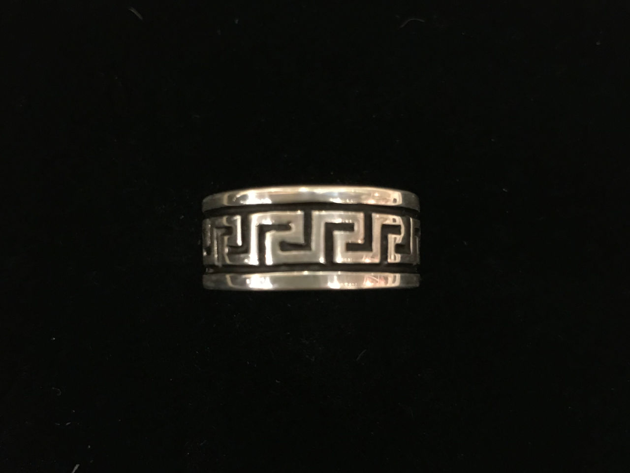 Sterling silver ring with black border on each edge and symmetrical lined design