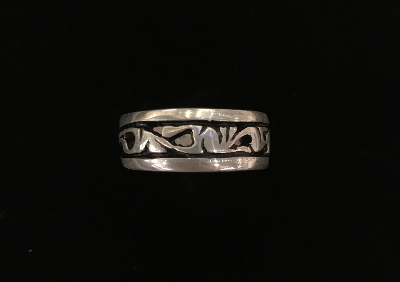sterling silver ring with a black lined border on each edge and flow design in center.