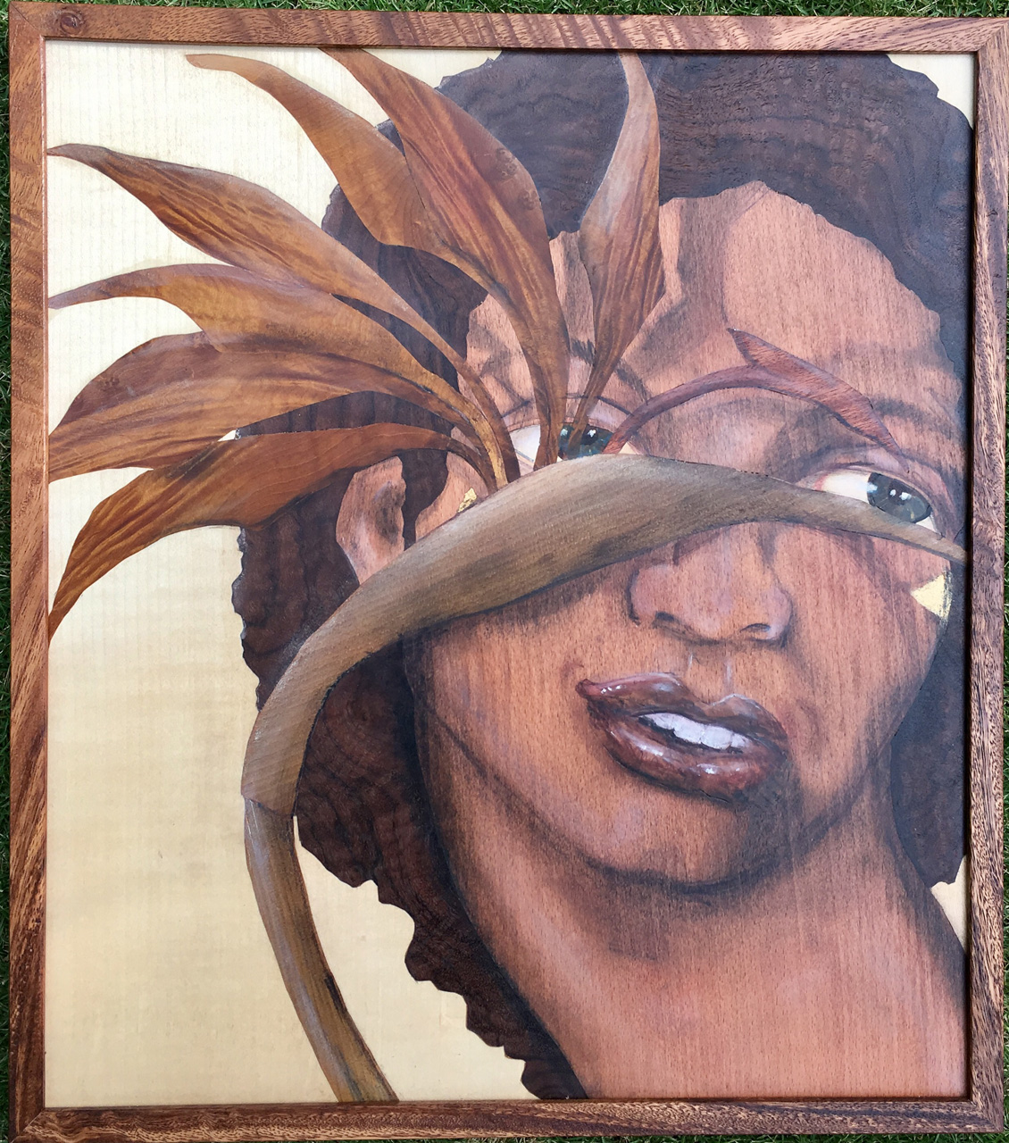See by Juli Morsella marquetry depicting a man's face behind a bird of paradise plant