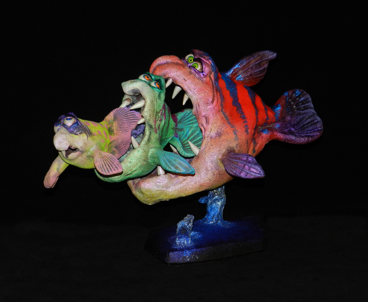Seafood by Steven Lee Smeltzer cartoonish whimsical clay sculpture of three fish eating each other
