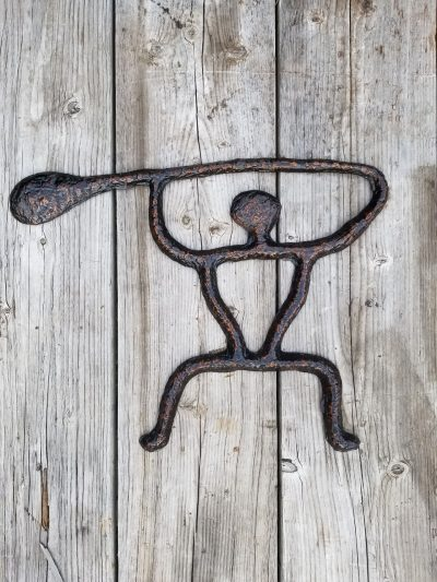 a wall hanging sculpture of a petroglyph paddler. A person holding a canoe paddle over their head.