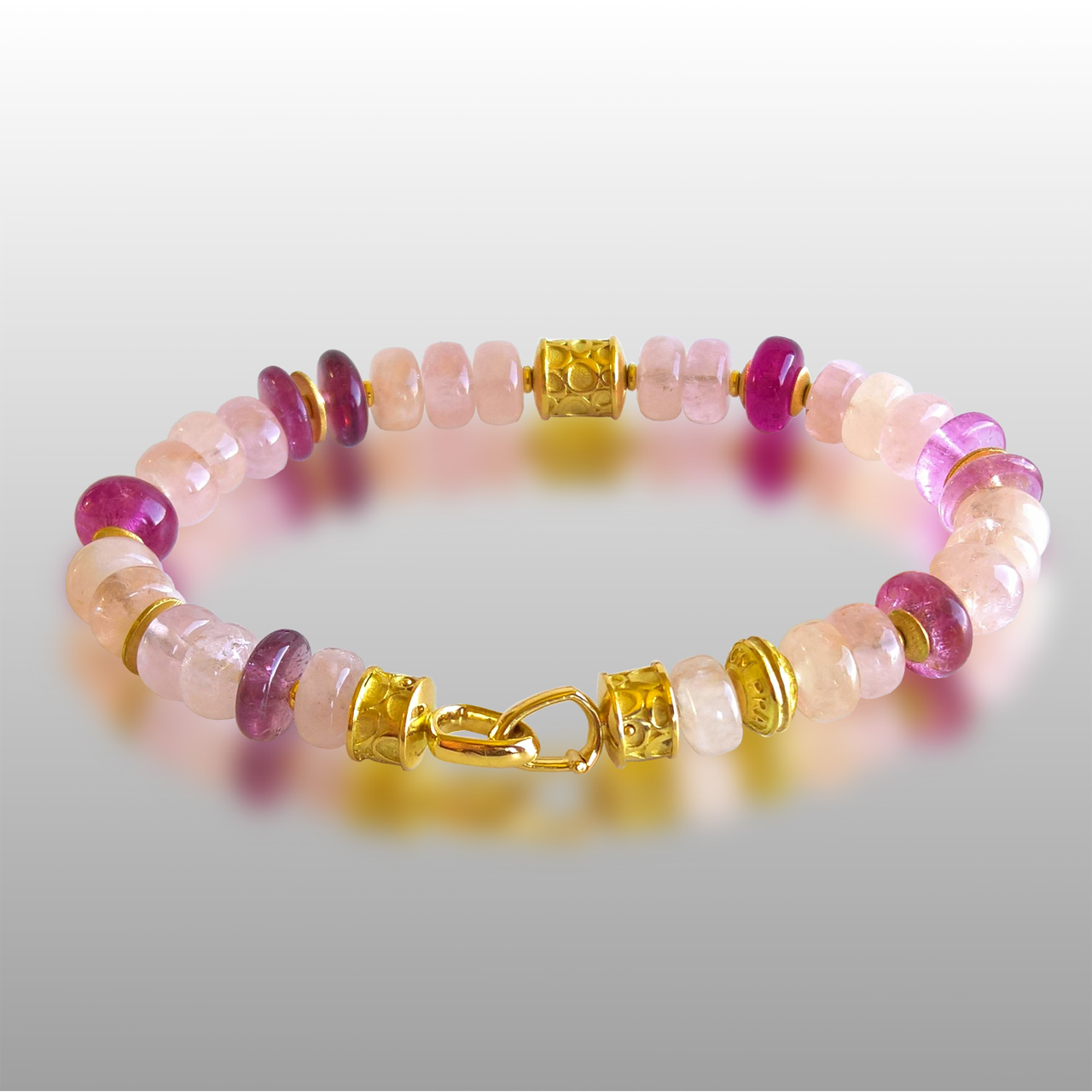 Bracelet made of various shades of pink stones and gold beads and clasp