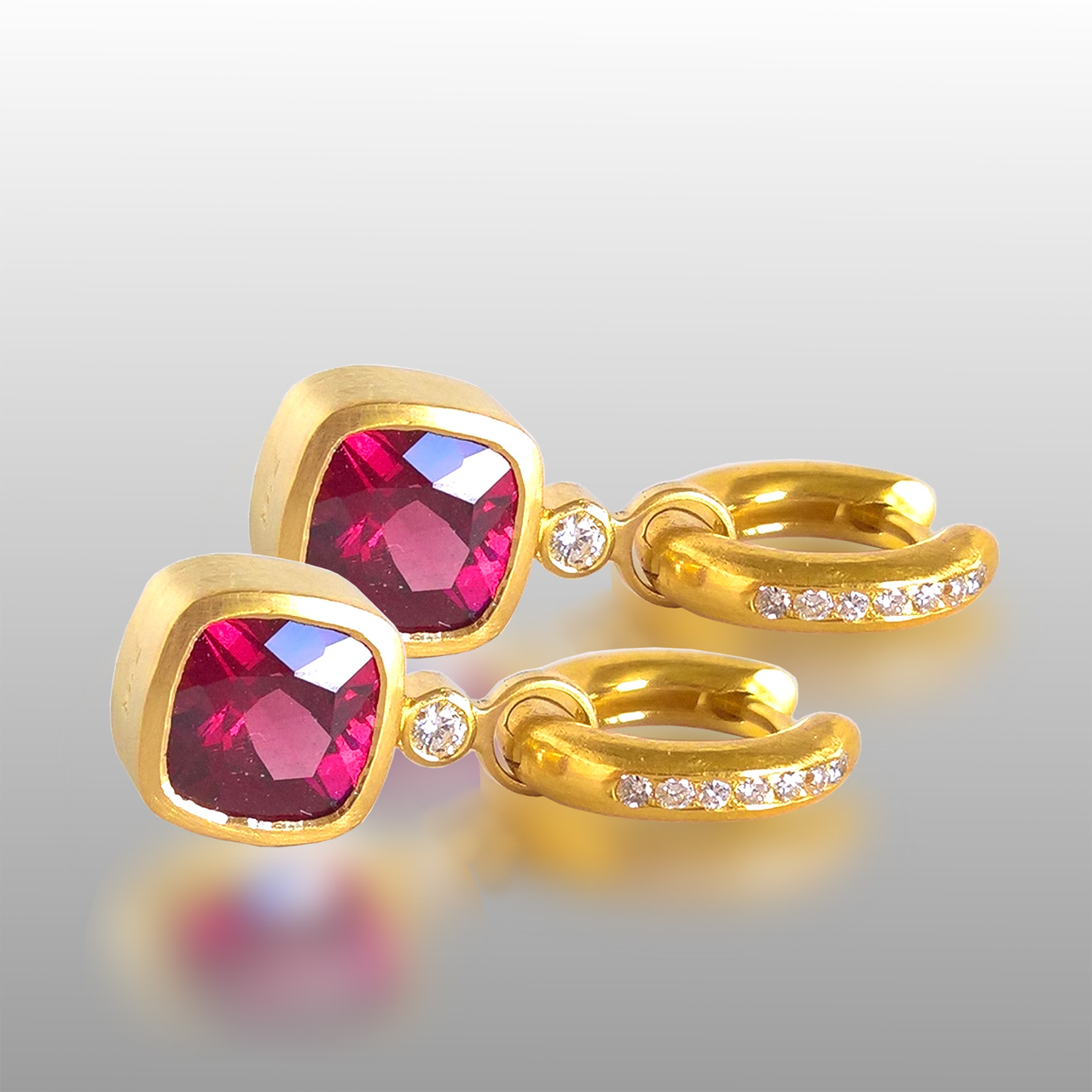 Small gold hoops with diamonds and magenta stones hanging