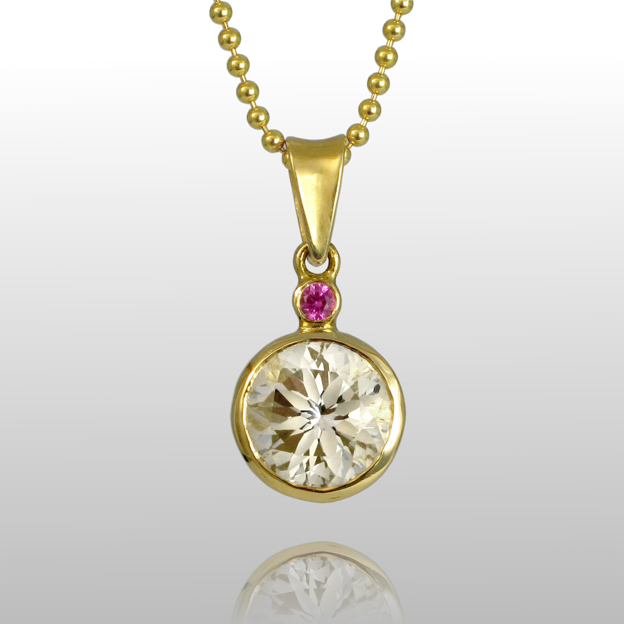 18k yellow gold pendant and a diamond and a small single pink gemstone above