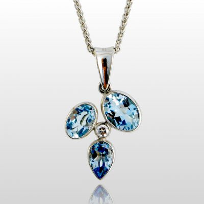 White gold pendant with 3 blue stones and a single diamond in the center