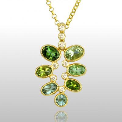 Gold pendant with 7 green stones, all different shades of green. And diamonds.