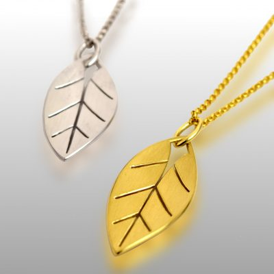 Two leaf pendants - one made of white gold and one made of yellow gold