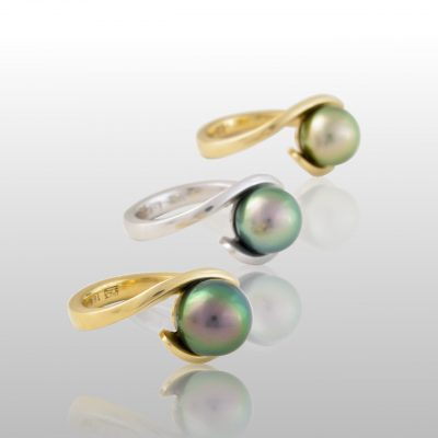 Three Tahitian pearl rings. Thin gold bands which wrap around the pearl