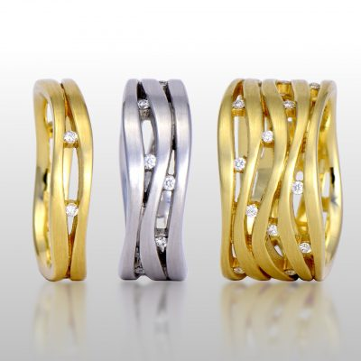 Three rings, two are yellow gold and one is white gold. All various widths and diamonds