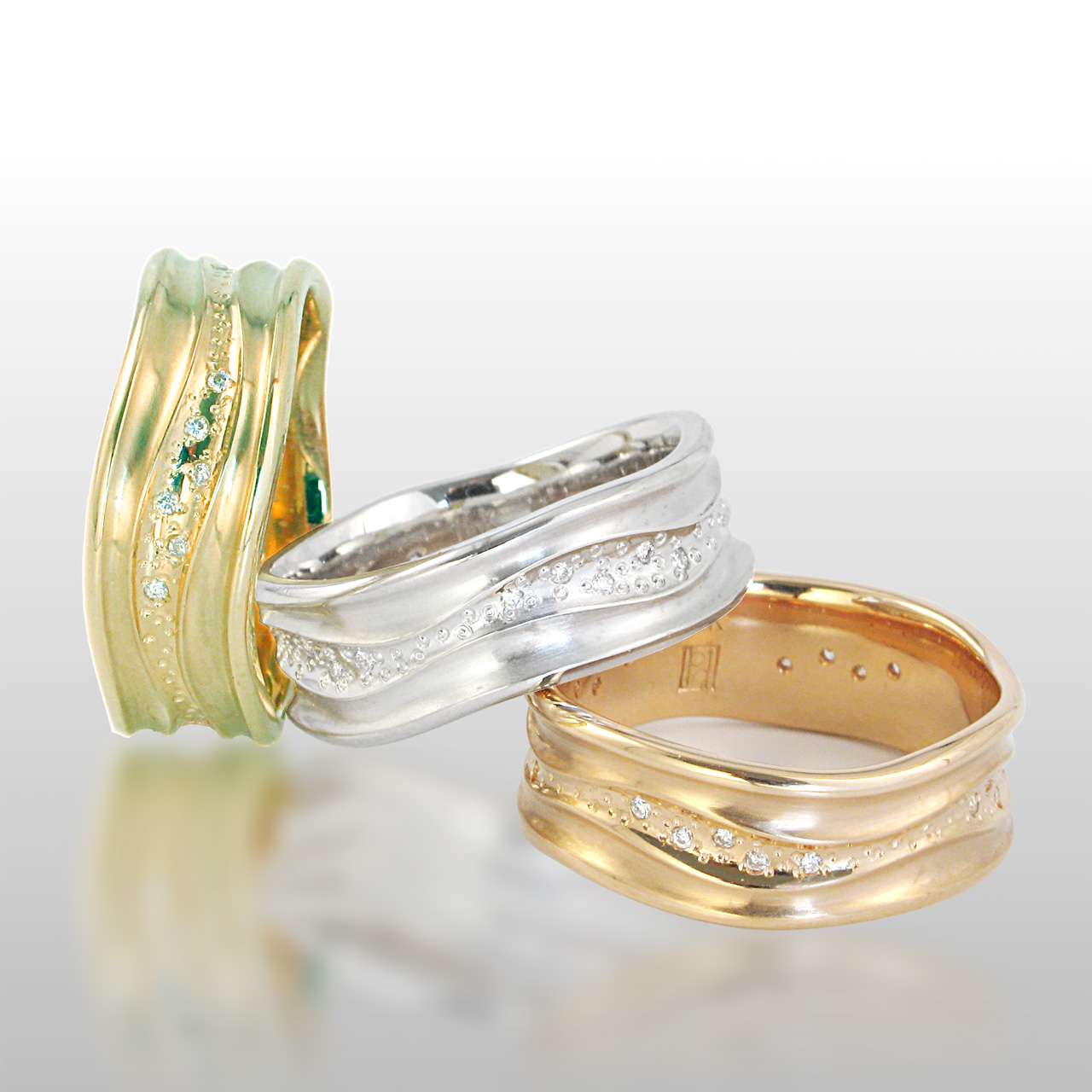 three wide band rings - one in yellow, white and rose gold. Curvy lines and diamonds set in the center