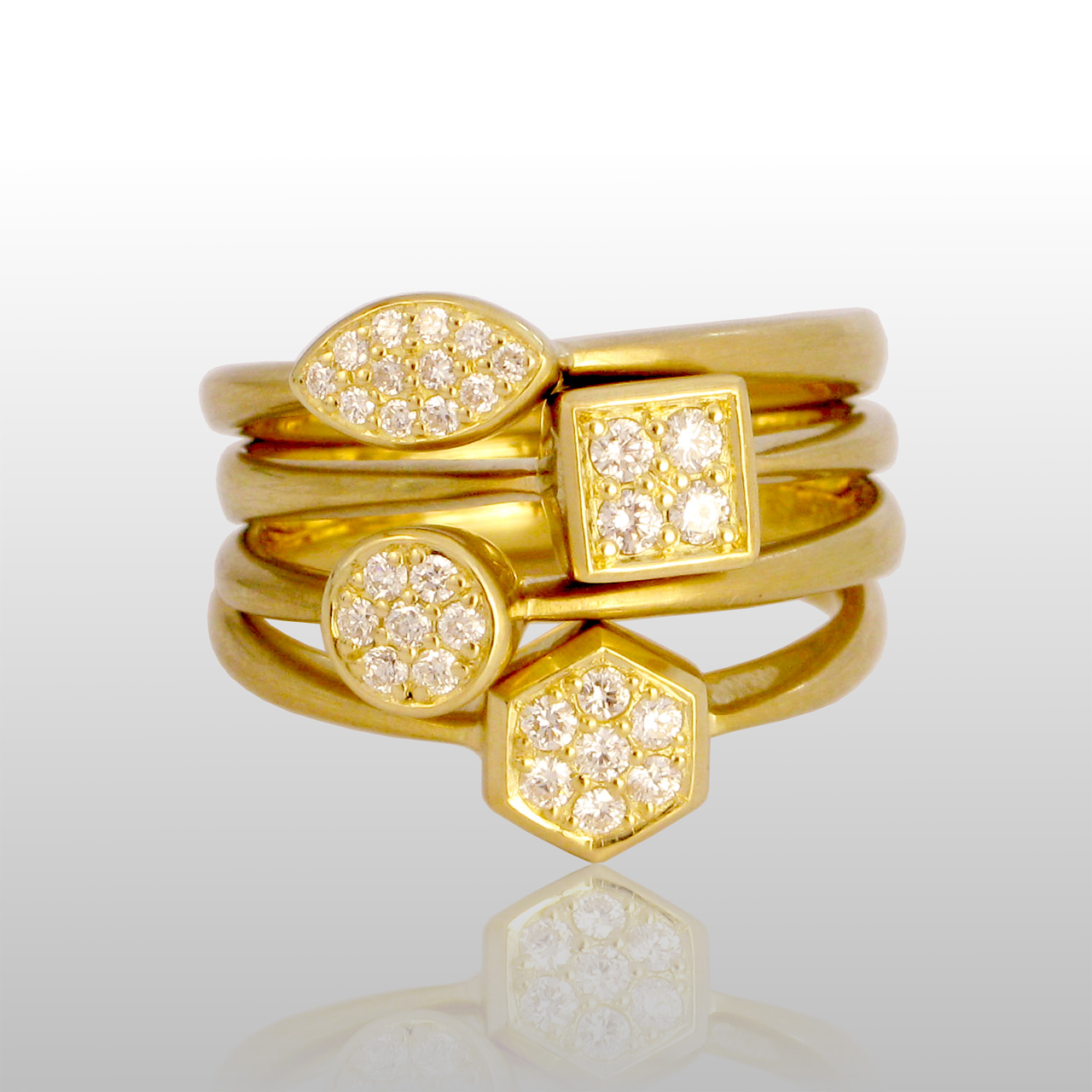 5 gold rings with various shapes and small diamonds in the center of each