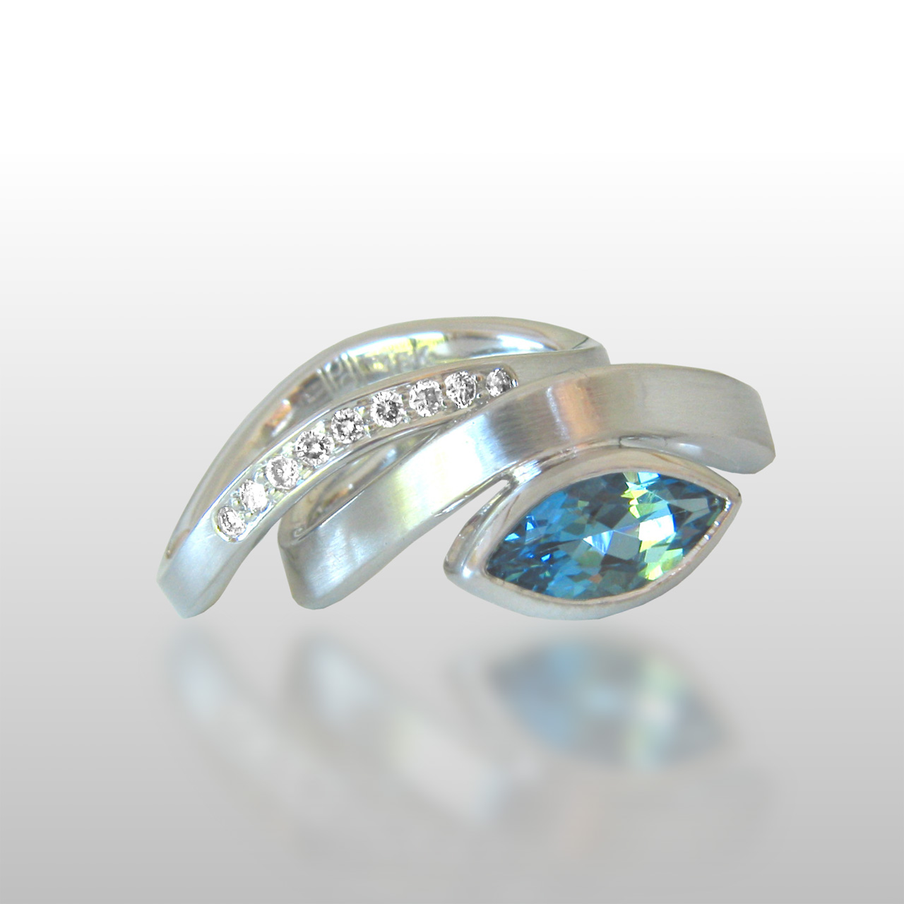 White gold ring set with a set of small diamonds and one large aquamarine stone cut into a unique shape