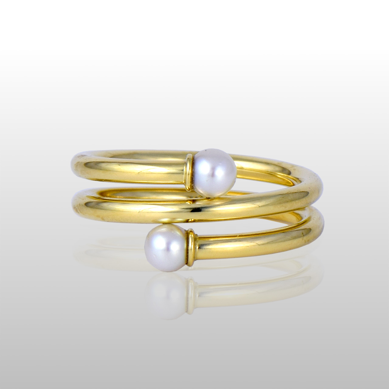 Gold spiral ring with with two pearls on each end.