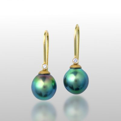 Tahitian Pearl earrings with a diamond on each side. Ear wires are made of 18k gold. Dangle earrings