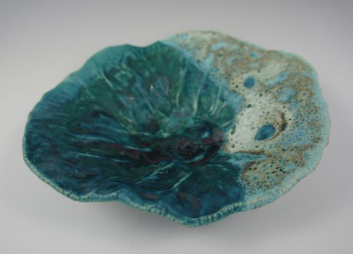 A small organic shaped bowl with various colors of blue