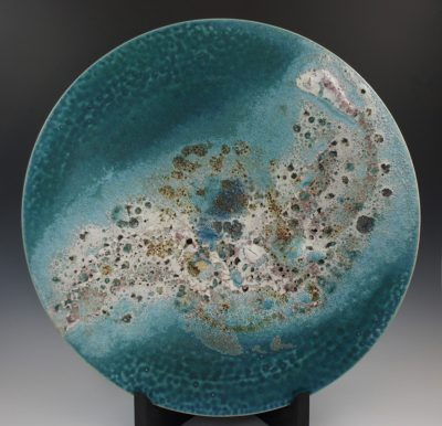 A aqua blue plate shaped round with sea foam like designs in the center