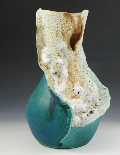 A aqua and terracotta colored vase with white bubbles to resemble sea foam
