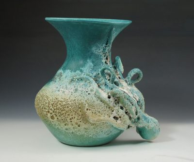A aqua and terracotta colored vase with a single octopus figure wrapped bottom of the vase