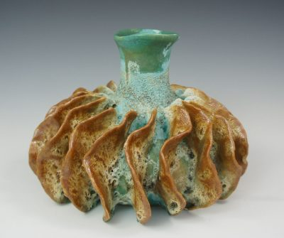 A ceramic vase sea foam green and terracotta color. Organic lines to resemble a sea urchin