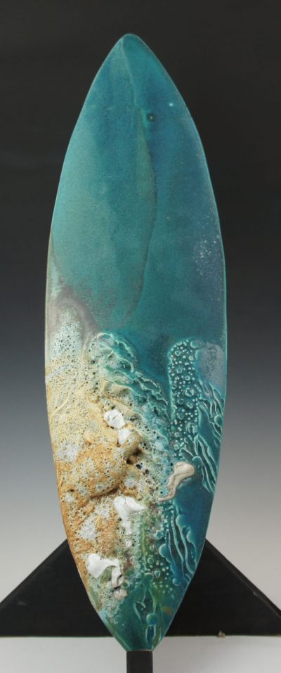 A surfboard shaped sculpture with blues, rust colors, greens, and white bubbles to resemble sea foam