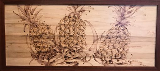 A wood burned wood panel of three details pineapple fruits