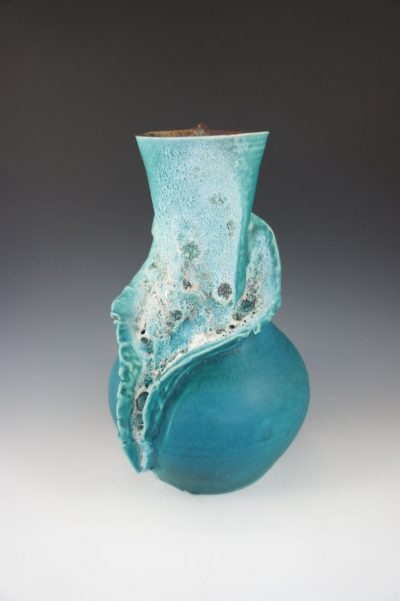 An aqua colored vase with white see foam design and a single turtle