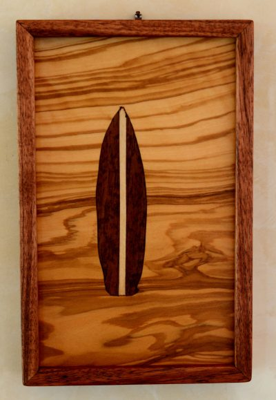 A wall hanging marquetry piece of a surfboard made of dark wood, in the center of a lighter wood with striations