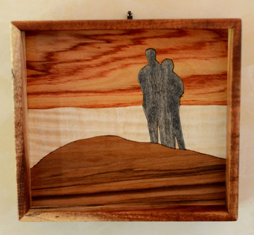a wall hanging made of various woods, of a couple standing side by side on sand dunes, looking out at a sunset