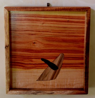 A square wall hanging made of various woods, of a humpback whale breaching out of the water